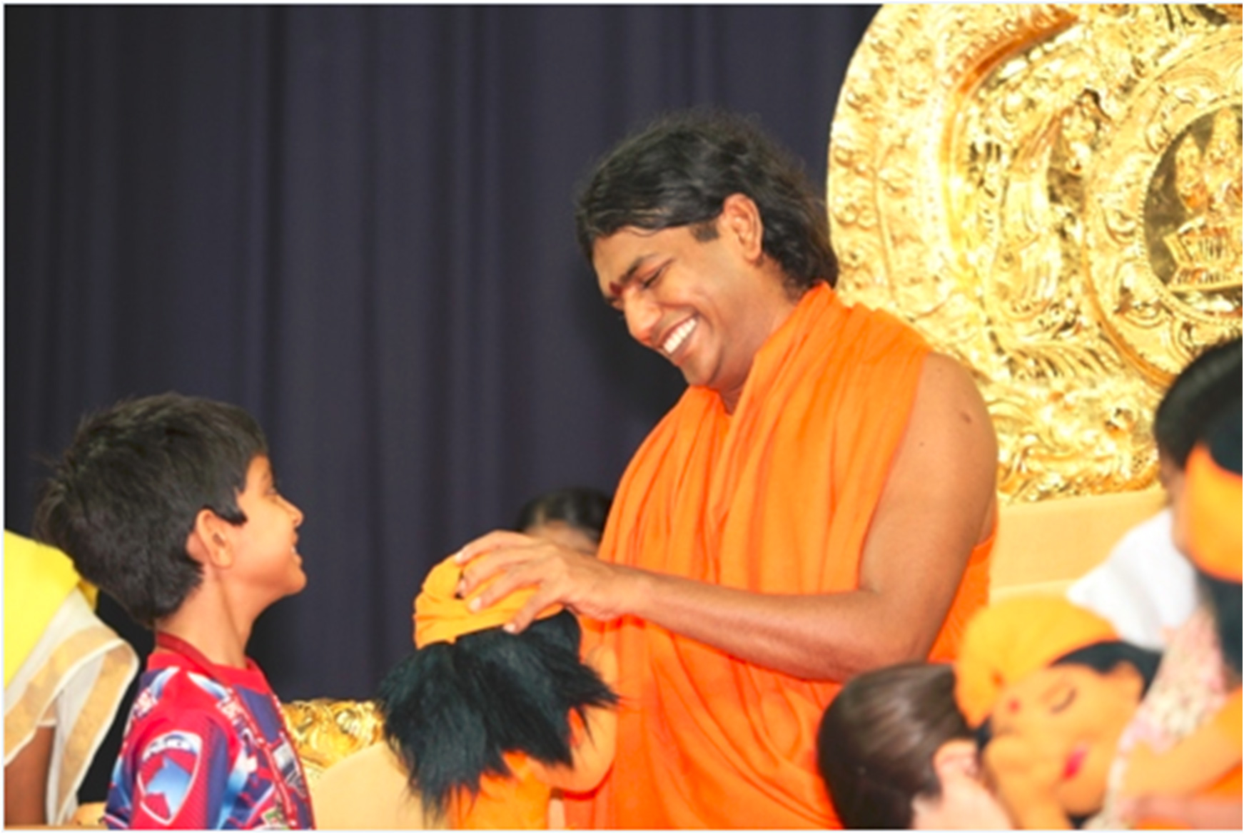 Swamiji laughing with the children and blessing their toys