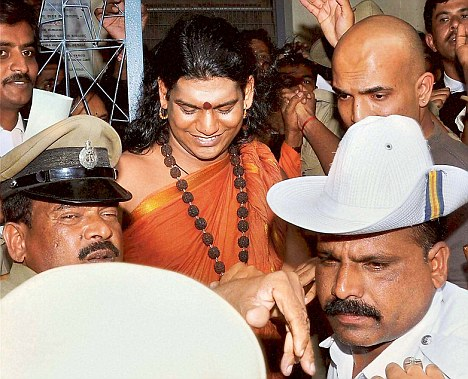 Bengaluru : Police take away Swami Nityananda after he surrendered before a magistrate at a court in Ramanagara near Bengaluru on Wednesday. PTI Photo(PTI6_13_2012_000105B)